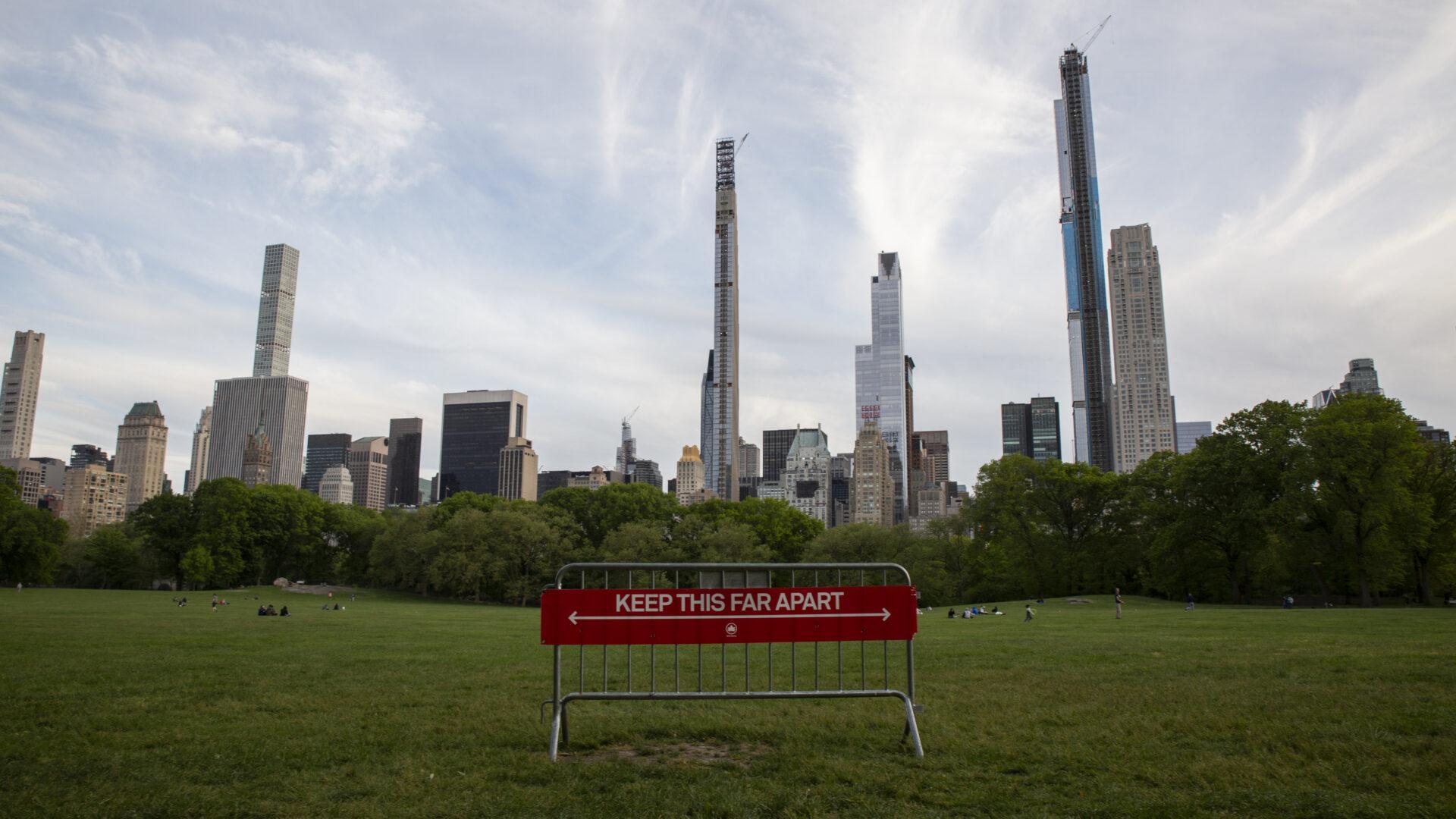 """Keskuspuisto Manhattanilla, New Yorkissa. Nurmella kyltti, jossa teksti: """"Keep this far apart"""". Taustalla pilvenpiirtäjiä."""