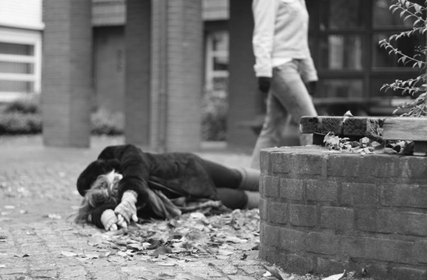 Mustavalkoinen kuva, henkilö makaa kivikadulla, häntä ympäröi syksyiset puunlehdet. Toinen henkilö kävelee ohi taustalla.