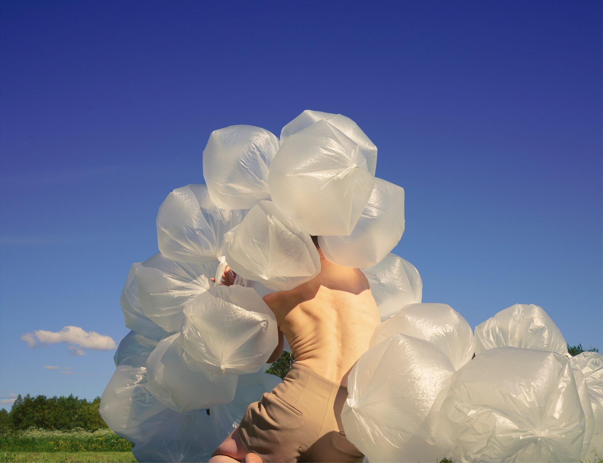 Istuvan henkilön paljasta selkää ympäröi ilmalla täytetyt muovipussit. Taustalla näkyy sininen taivas, vihreä nurmikko ja kuusimetsä.