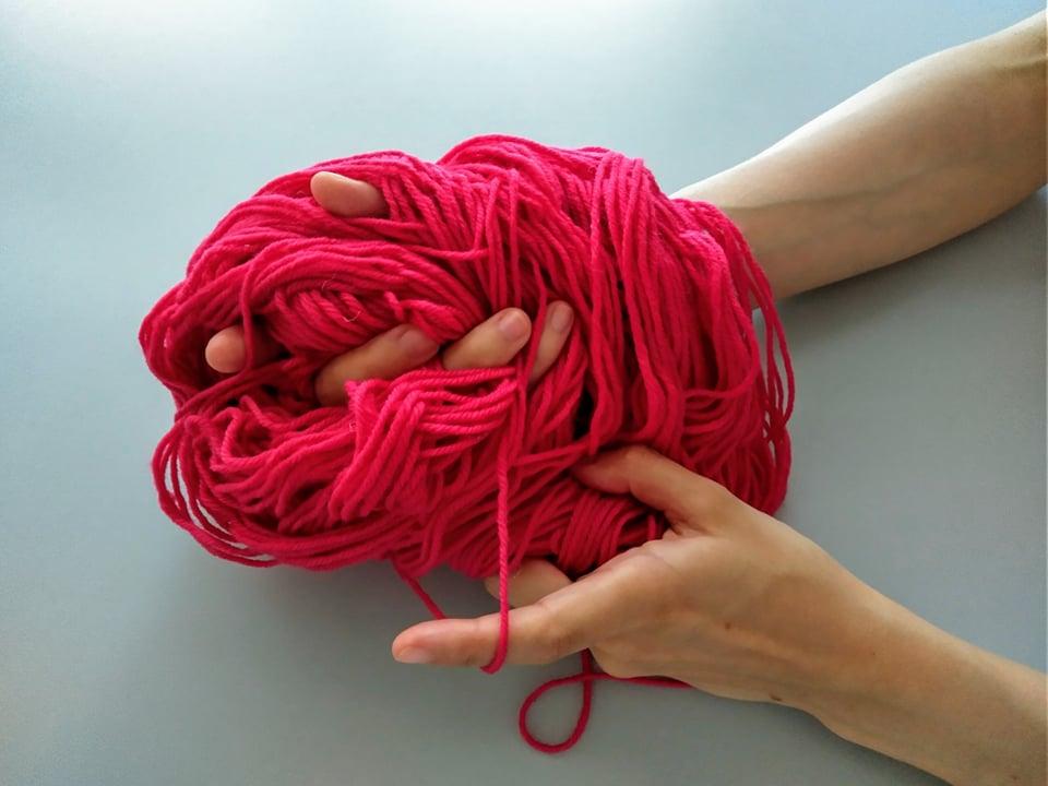 Hajoavasta lankakerä, jonka lävitse kulkeutuvat kädet.