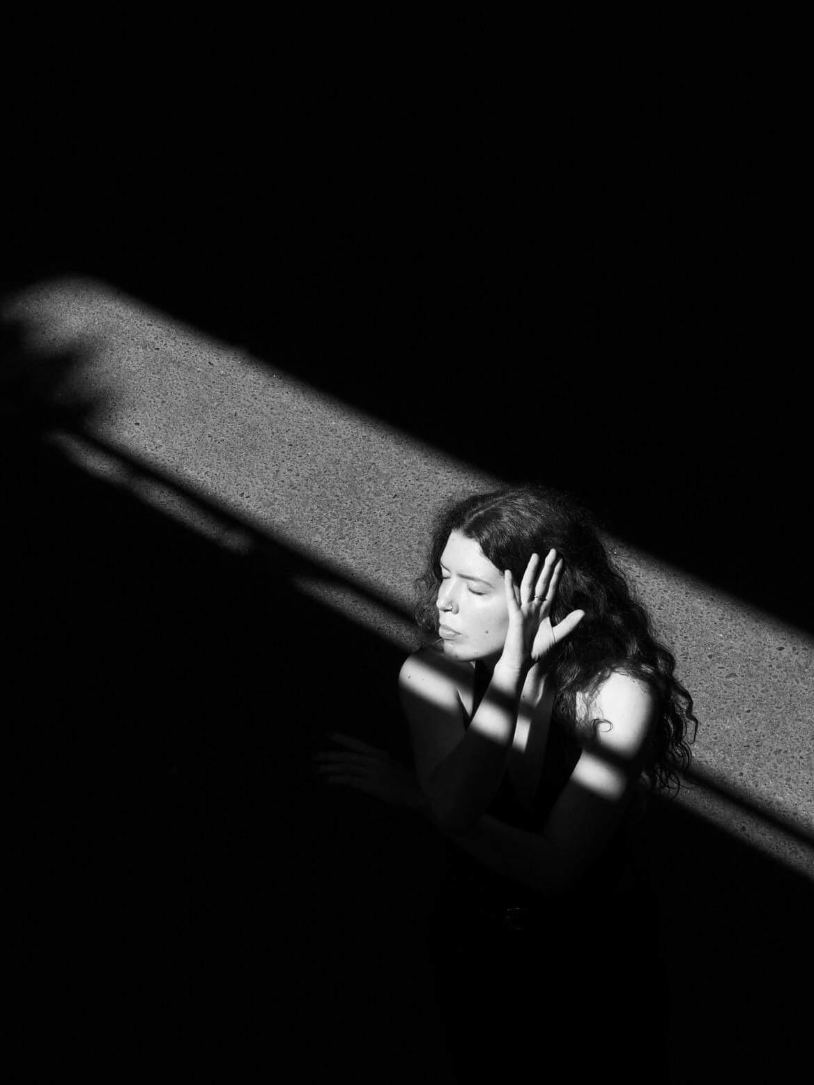 Nainen varjossa, valo heijastuu vain kasvoihin. Hänen silmänsä ovat kiinni ja hän on kääntänyt kasvonsa vasempaan, käsi kasvojen vieressä.