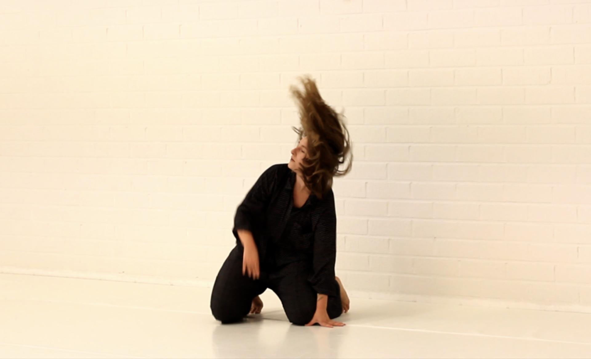 Henkilö kesken tanssin, polvillaan ja tukka hulmuten.