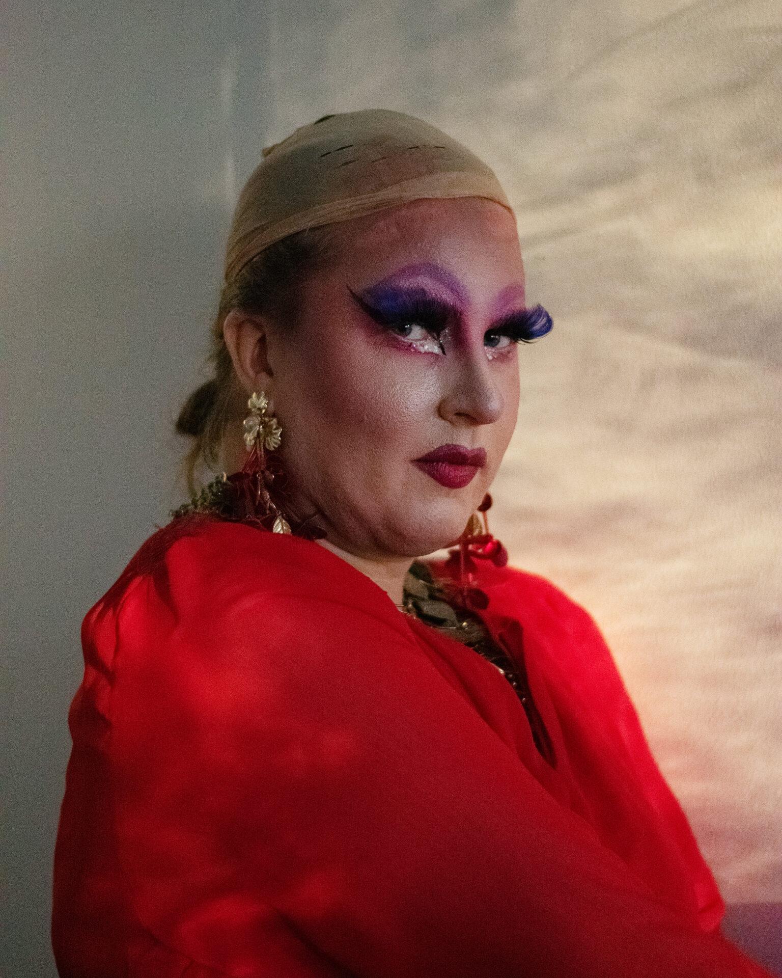 Henkilö, jolla on drag-tyylisesti meikkiä, peruukkisukka ja punainen mekko päällään.